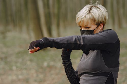 Strong sportswoman doing punching workout in park