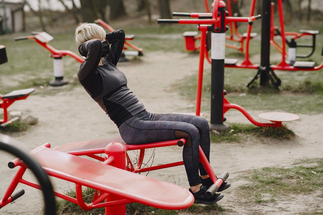 Full length side view of anonymous female in sportswear and protective black mask with hands behind head working out at street simulator