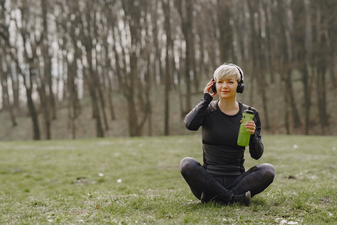 Young fit woman in headphones sitting on ground holding bottle of water and listening to music