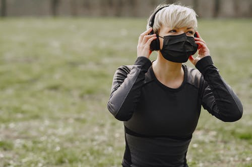 Young woman with protective mask and headphones having rest after workout in park