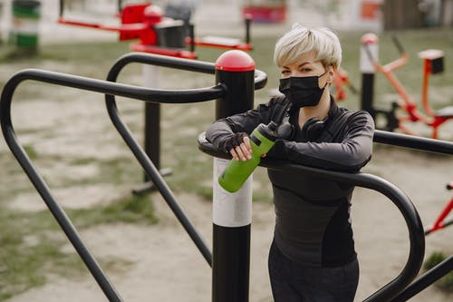 Young woman in protective mask holding bottle of water while working out at street simulator