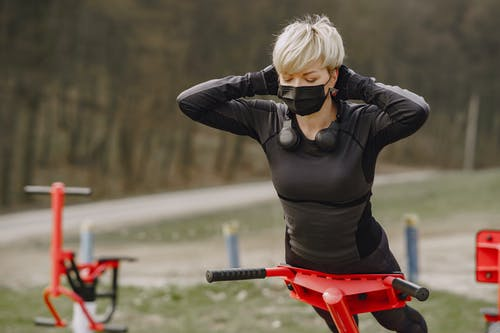 Young woman in protective mask doing hyperextension exercise outdoors