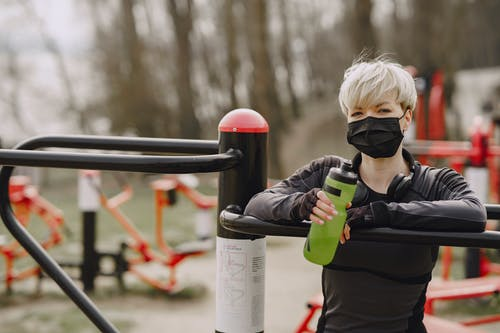 Stylish woman in medical mask with bottle of water on sports ground in street