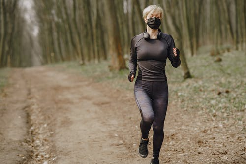 Fit woman in sportswear and mask jogging along forest alley during virus outbreak