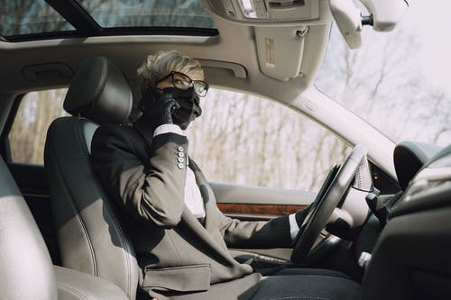 From below side view of unrecognizable woman in formal clothes and protective mask and gloves talking on cellphone while driving contemporary car