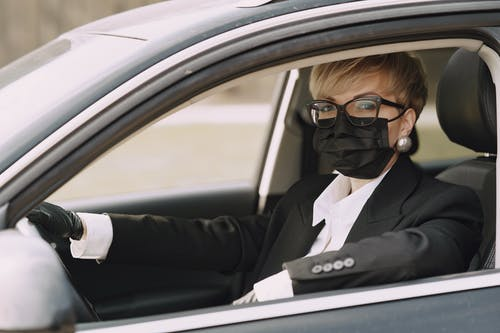 Serious female driver in protective mask and gloves in car