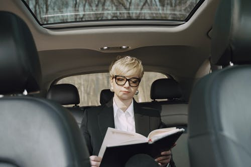 From below of concentrated female entrepreneur in elegant formal clothes sitting on backseat while reading memos in notebook riding in car