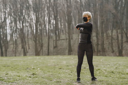 Full body of sportswoman in medical mask warming up before training in forest during outbreak of virus