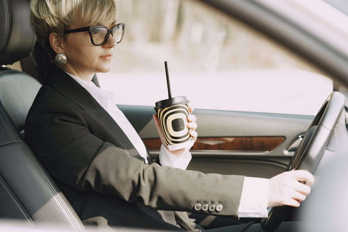 Stylish woman with takeaway coffee driving car