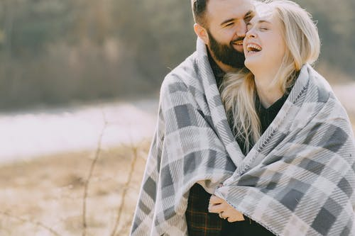 Happy couple hugging under plaid in nature
