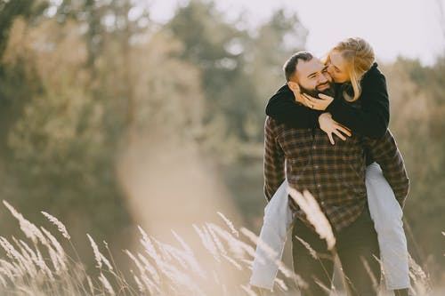 Happy man carrying girlfriend on back in forest