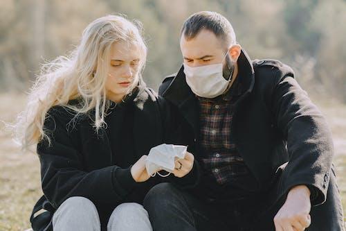 Man in Black Jacket Sitting Beside Woman in Black Jacket