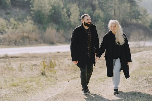 Full length happy couple walking on rural road