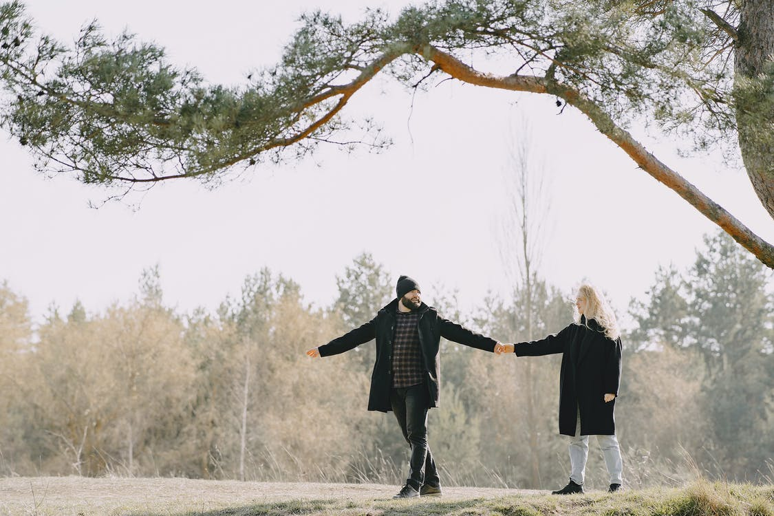 Full body of cheerful couple strolling together near tree in countryside
