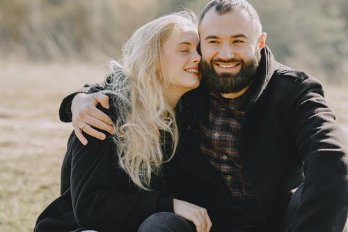 Man in Black Jacket Hugging Woman in Black Long Sleeve Shirt
