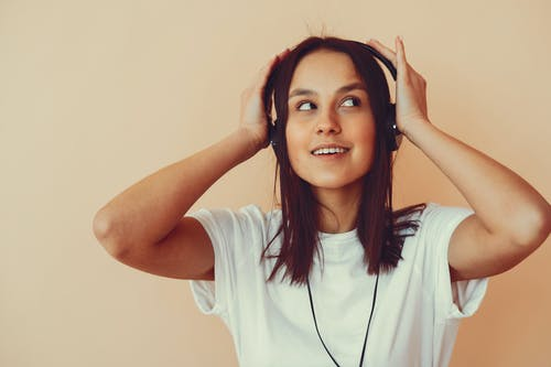 Dreamy young woman listening to music in headphones