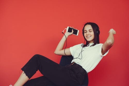 Content woman sitting on chair and enjoying music in headphones