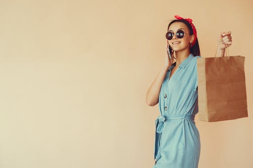 Woman in Blue Sleeveless Dress Wearing Sunglasses