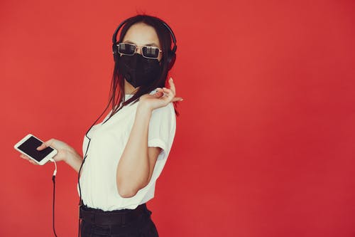 Trendy woman in respiratory mask listening to music in headphones
