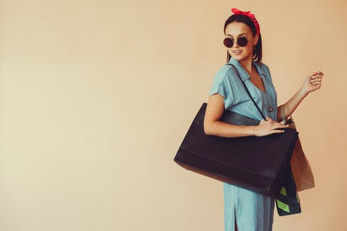 Content woman in stylish outfit with shopping bags