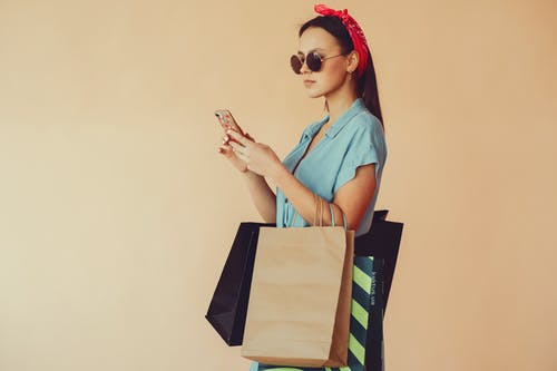 Calm woman with shopping bags using smartphone