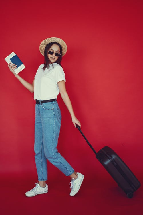 Stylish young lady walking with suitcase on red backdrop