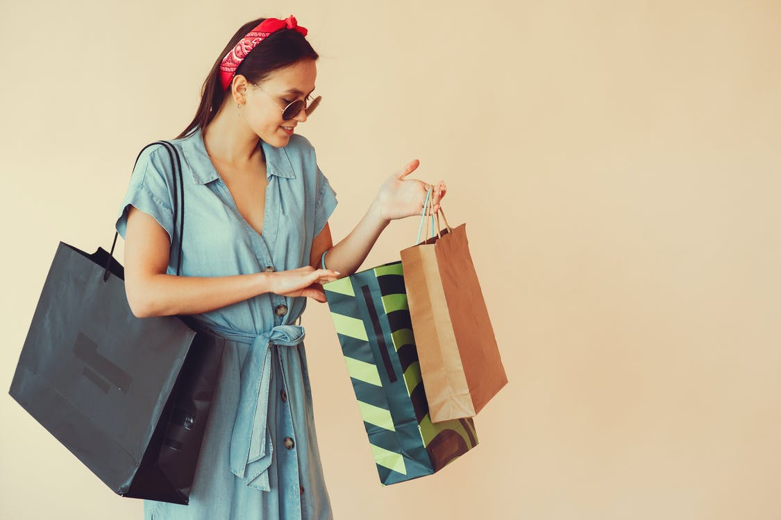 Happy young lady with shopping bags on beige background