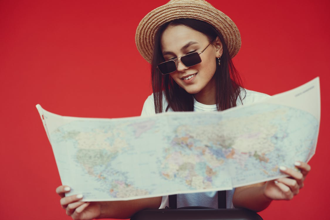 Smiling young woman in stylish hat and sunglasses choosing destination on paper map while standing with luggage on red background