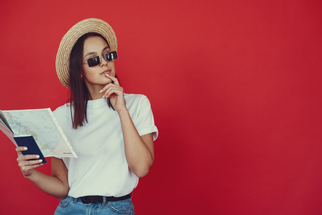 Thoughtful young woman in retro hat and trendy sunglasses holding map and touching chin while looking pensively away on red background
