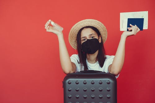 Young woman in medical mask and wicker hat holding passport and sanitizing spray while sitting behind suitcase and shrugging hand on red background