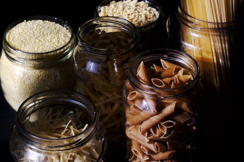 Different types of pastas and cereals in glass jars on kitchen in sunlight