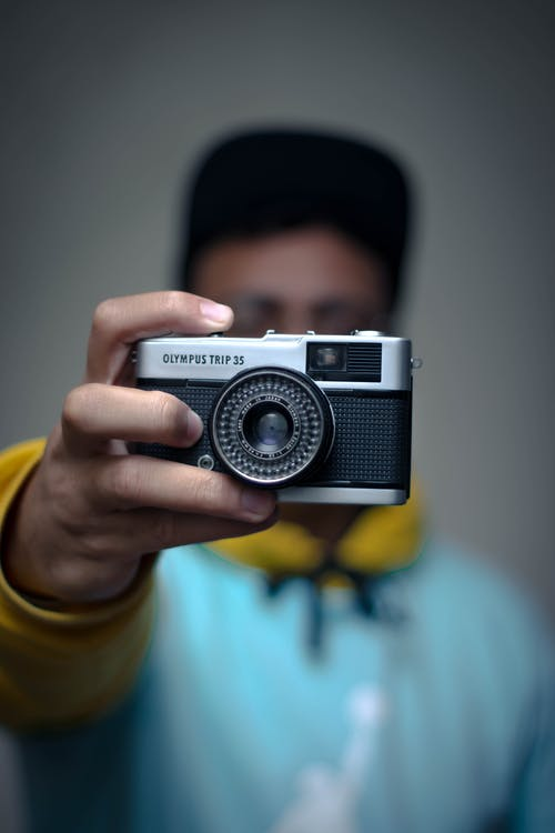 Faceless man using vintage photo camera