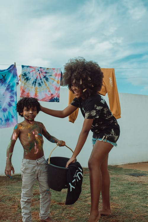Full body of young smiling African American woman in casual clothing with fluffy hair stroking hair of shirtless black boy holding bucket and looking at camera