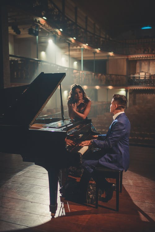 Man playing piano for woman