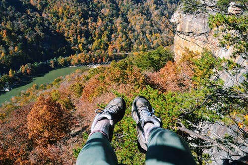Person in Black Hiking Shoes Sitting on Rock