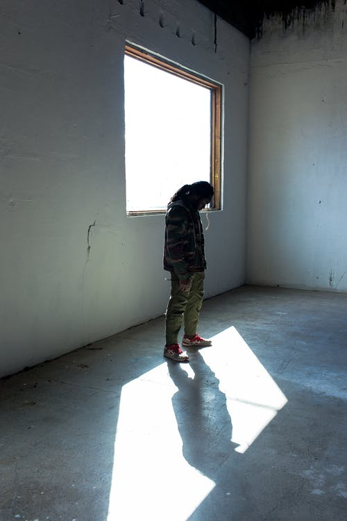 Full body of faceless stalker in warm clothing with hair tied up looking down while standing next to window in empty room of old shabby house in sunlight