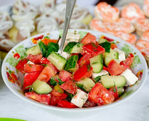 Salad of fresh cucumber and tomatoes mixed with cheese and parsley on table in bright room