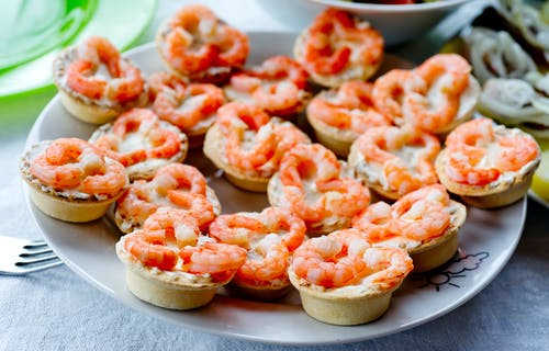 Peeled red boiled shrimps on tartlets on white plate on table in daylight in bright room