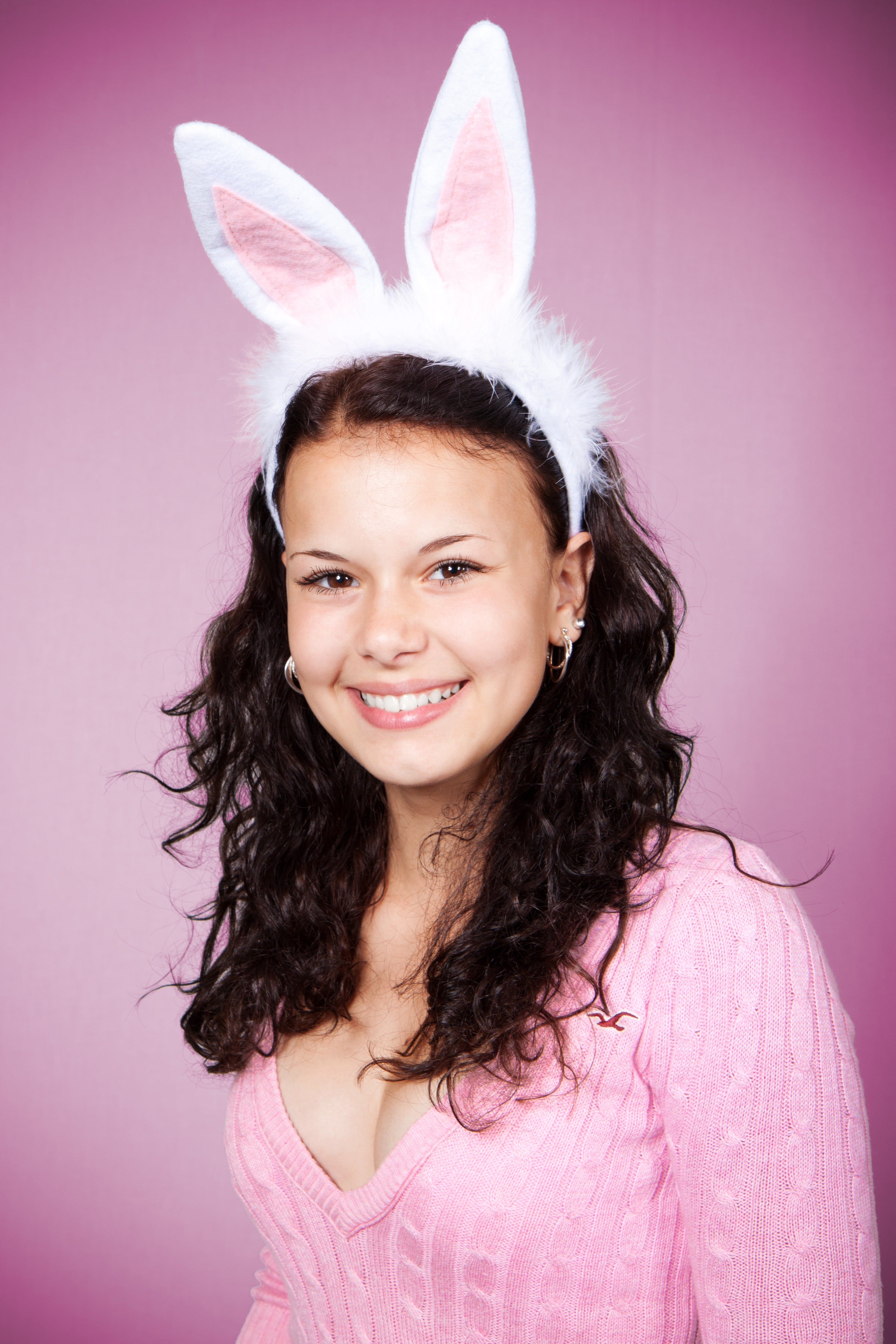 Woman in Pink Sweater Wearing Bunny Headband Smiling Against Pink Background