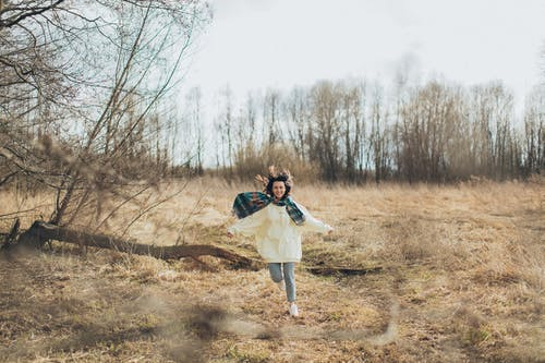 Full body of cheerful young female in warm clothes with hands outstretched running  along dry grass