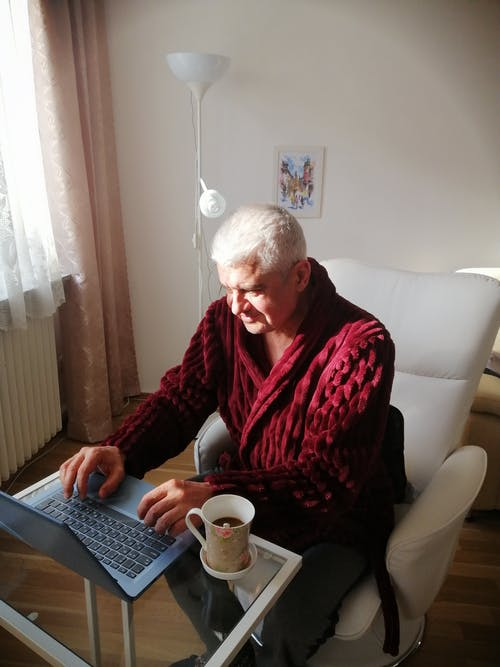 High angle of serious aged man in bathrobe having coffee while working remotely at home