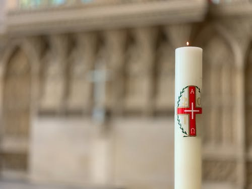 Burning candle with red cross