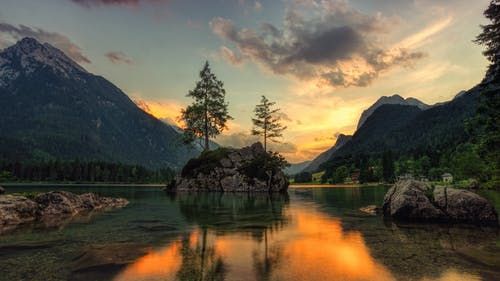 Amazing scenery of mountains and rock with trees in middle of lake with reflection of sunrise sky on water surface