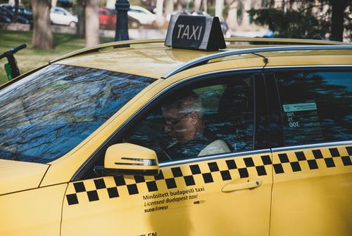 Taxi cab with male driver on street