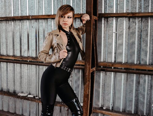 Serious young lady in stylish leather jacket leaning on metal fence and looking away while resting near rust construction