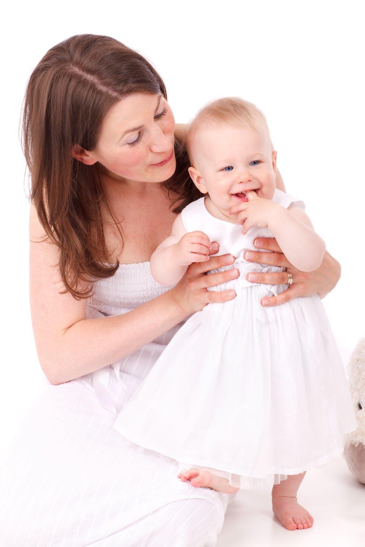 Mutter mit Baby in rosa Kleid | Quelle: Pexels