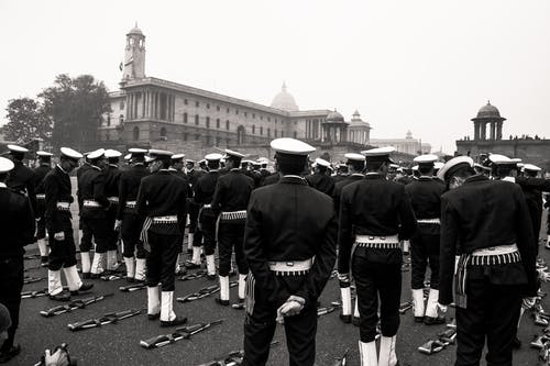 Black and white multiethnic men in military uniform standing in rows near automatic guns lying on ground during military parade on square near old buildings with turrets on daytime