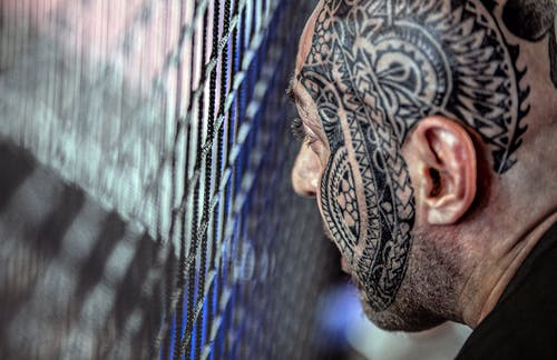 Crop ethnic man with tattoo on face near lattice