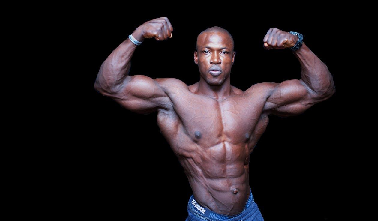 Shirtless ethnic bodybuilder demonstrating tense muscles on black background