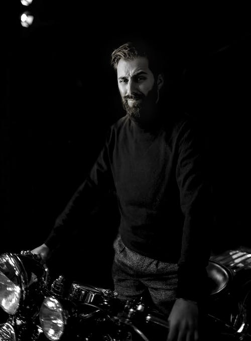 Black and white male in turtleneck standing with motorcycle on black background and looking at camera